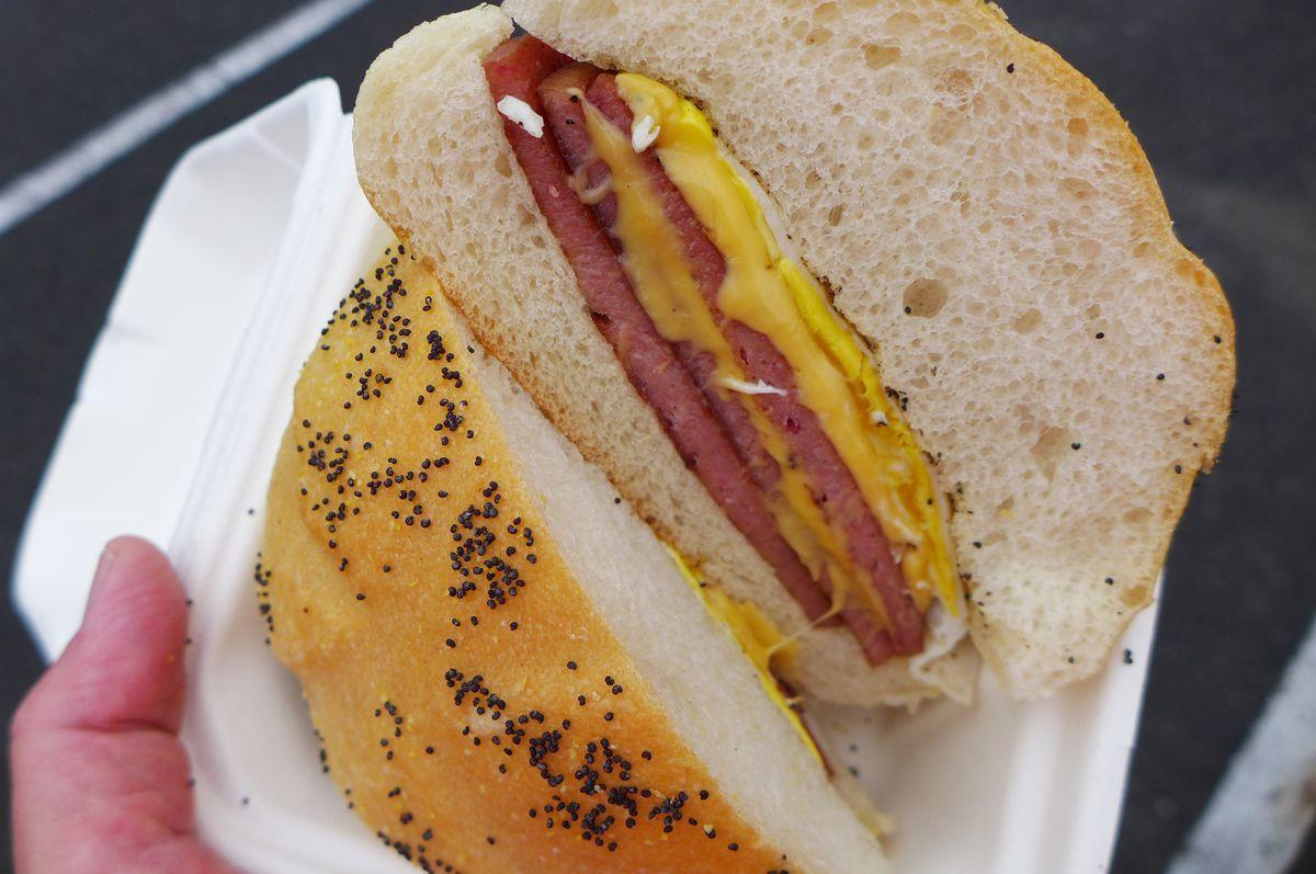 A breakfast sandwich of egg, cheese, and pork roll on a poppy seed roll but in half to show the cross section.