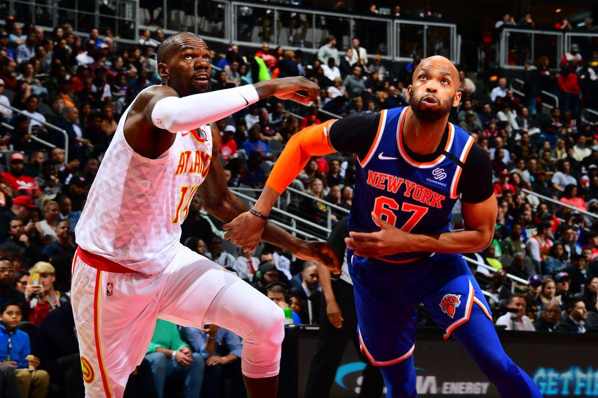 Dewayne Dedmon of the Atlanta Hawks and Taj Gibson of the New York Knicks go towards the basket on March 11, 2020 at State Farm Arena in Atlanta, Georgia.
