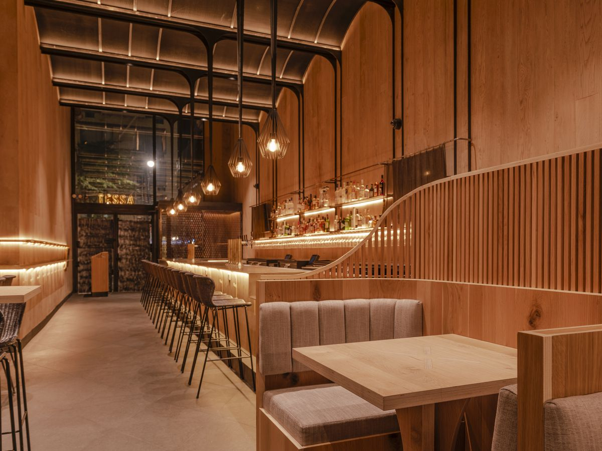 The bar at Tessa, with soaring ceilings and hanging lights