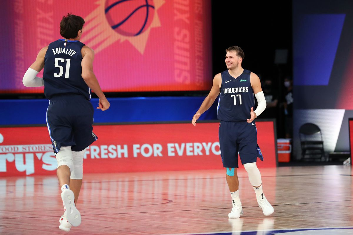 Luka Doncic of the Dallas Mavericks talks with Boban Marjanovic of the Dallas Mavericks during the game against the Phoenix Suns on August 2, 2020 at The Visa Athletic Center at ESPN Wide World Of Sports Complex in Reunion, Florida.
