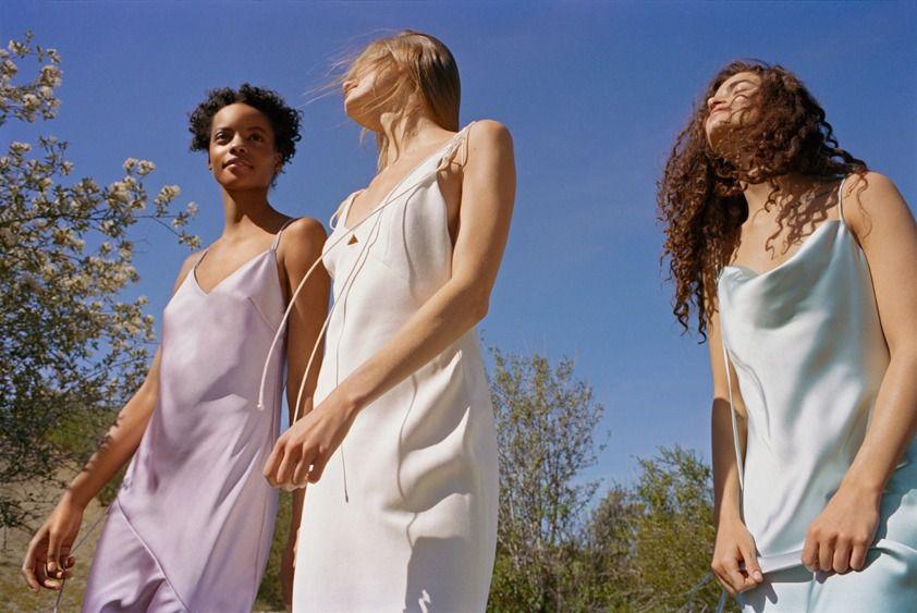 Women wearing Topshop bridesmaid dresses, walking outside in a field