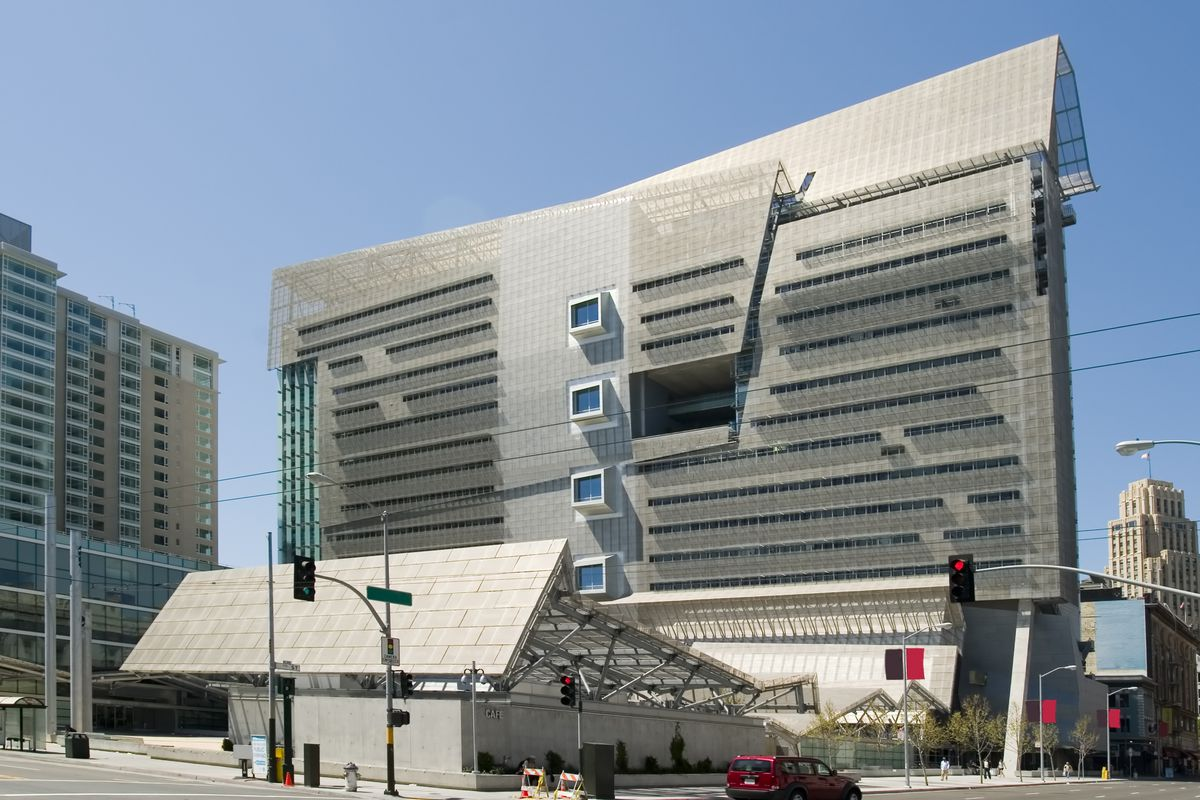 A tall building with a flat, rectangular profile, a series of protruding three-story atriums down the center, and a huge, cube-shaped alcove set into the face of the building next to them.
