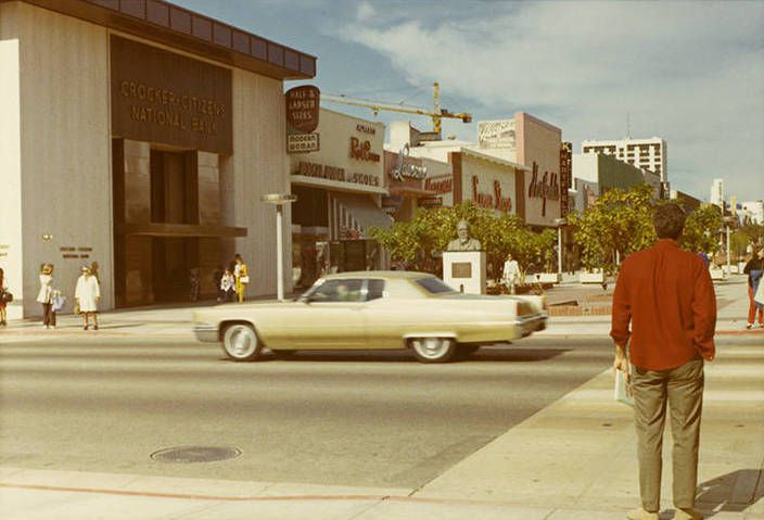Vintage photo of a downtown street where people are walking in front of small shops.