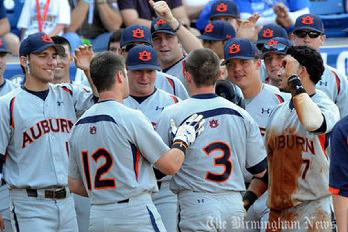 Auburn's Justin Bryant is greeted at home plate by his teammates after a third inning home run against Georgia in the SEC Tournament. (<em>photo, Todd Van Ernst</em>)