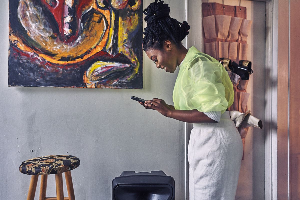 Francesca Chaney uses her phone to select music to play on the speaker at her feet.