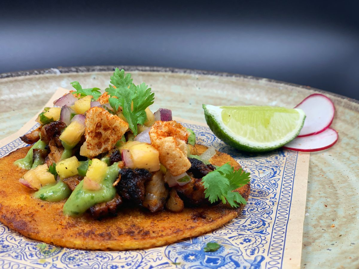 A taco sits on brown paper covered with a blue pattern, on a beige plate. The taco is topped with pork, pineapple, cilantro, and other ingredients, and there's a slice of lime and radishes to the side.