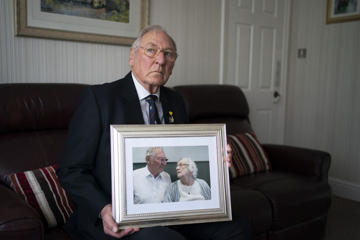 Gordon Bonner holds one of his favorite photographs of him with his late wife Muriel who, in April 2020 died of COVID-19, at his home in Leeds, England, Saturday Jan. 23, 2021.