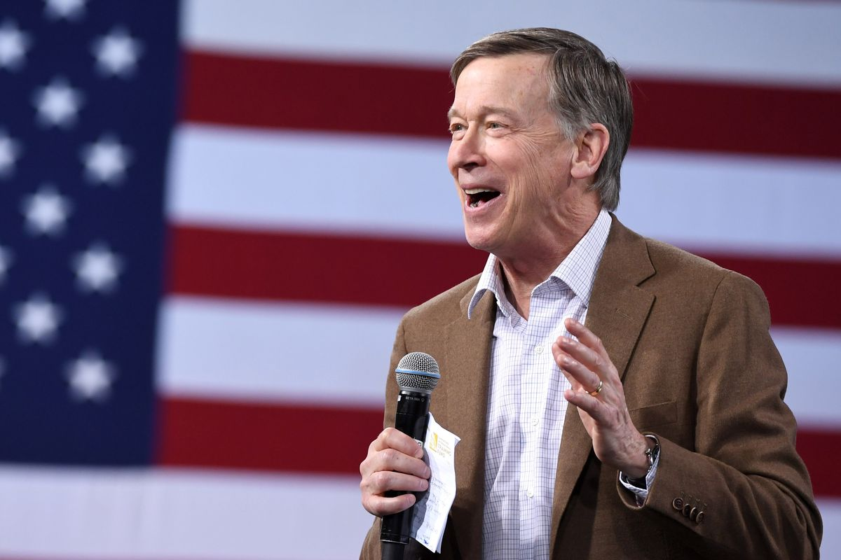 John Hickenlooper holding a microphone in front of an American flag background.