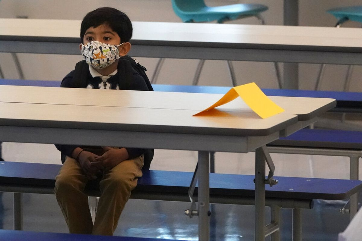 A student waits in the cafeteria the first day of school at Washington Elementary School in Riviera Beach, Florida.