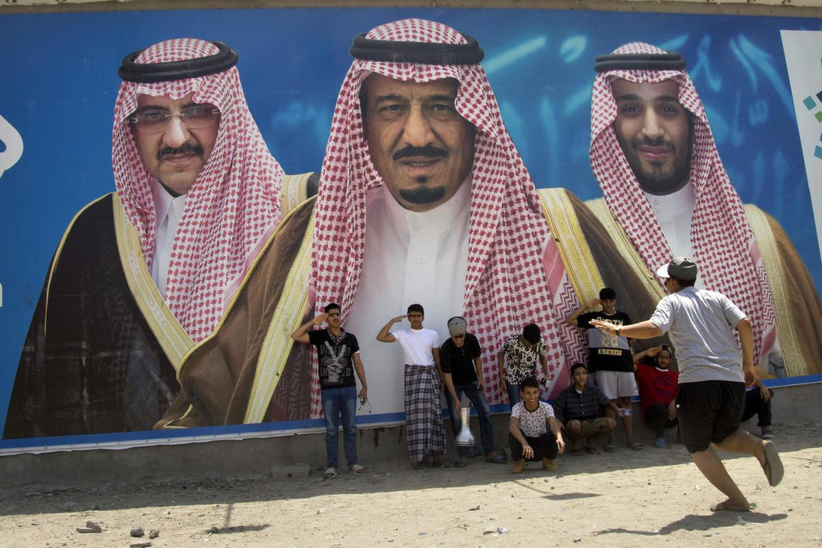 FILE - In this April 4, 2017, file picture Saudi boys pose in front of a huge billboard showing in the center, King Salman, with his 31-year-old son Mohammed bin Salman to the right, and Prince Mohammed bin Nayef to the left in Taif, Saudi Arabia. Salman