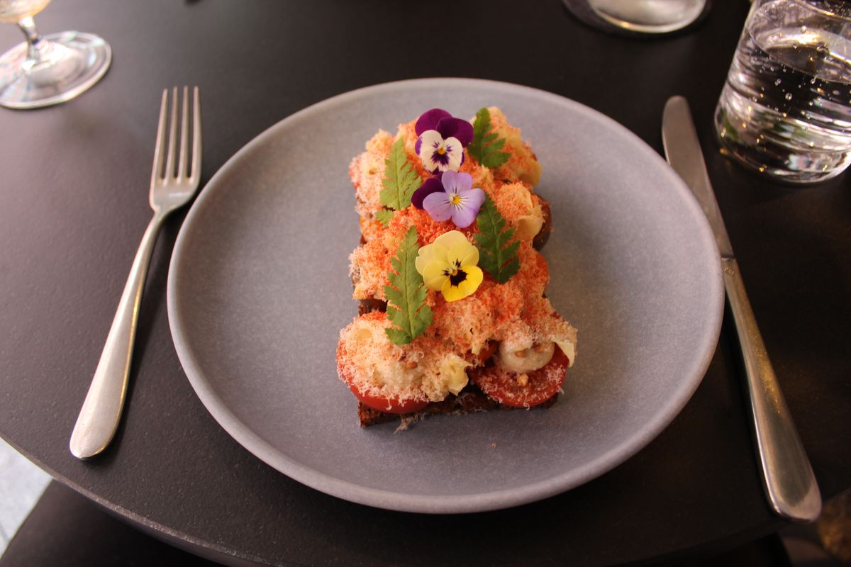An open-faced sandwich decorated with a thick layer of toppings including fish and grated cheese, topped with colorful flowers and small leaves.