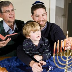 Three generations of a Jewish family light a Hanukkah menorah. Jews involve multiple generations, teaching their beliefs and traditions to children in the home to preserve the faith.
