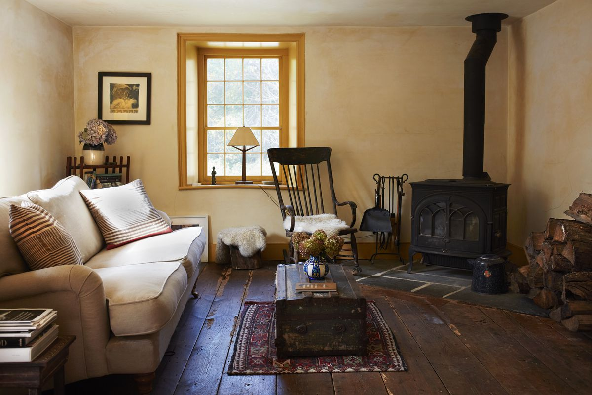 A black, wood-burning stove is in the corner of the living room.