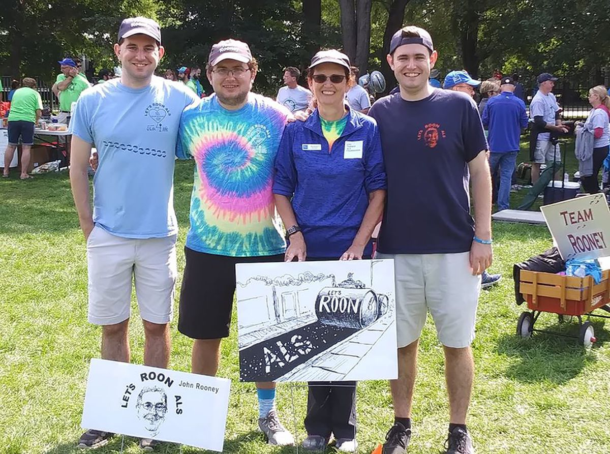 """Meg Rooney (holding placard) at the 2019 Les Turner ALS Foundation Walk for Life at Soldier Field with sons (from left) Ned, Dan and Jack. She volunteered with ALS support groups, counseling members. """"Just over a week ago, she popped in in a video chat for the support group and stayed with us on the support group call,"""" said foundation CEO Andrea Pauls Backman."""