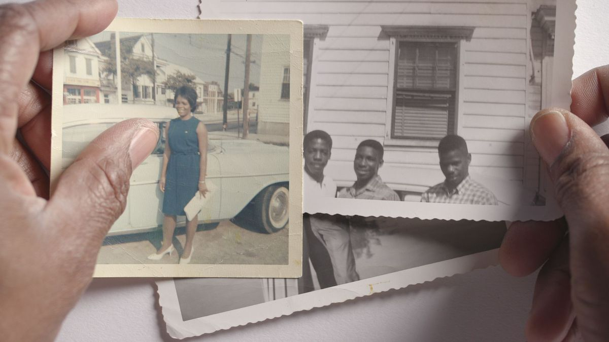 Strong Island: a Black man's hands hold old photos of a woman in a green dress and three young boys