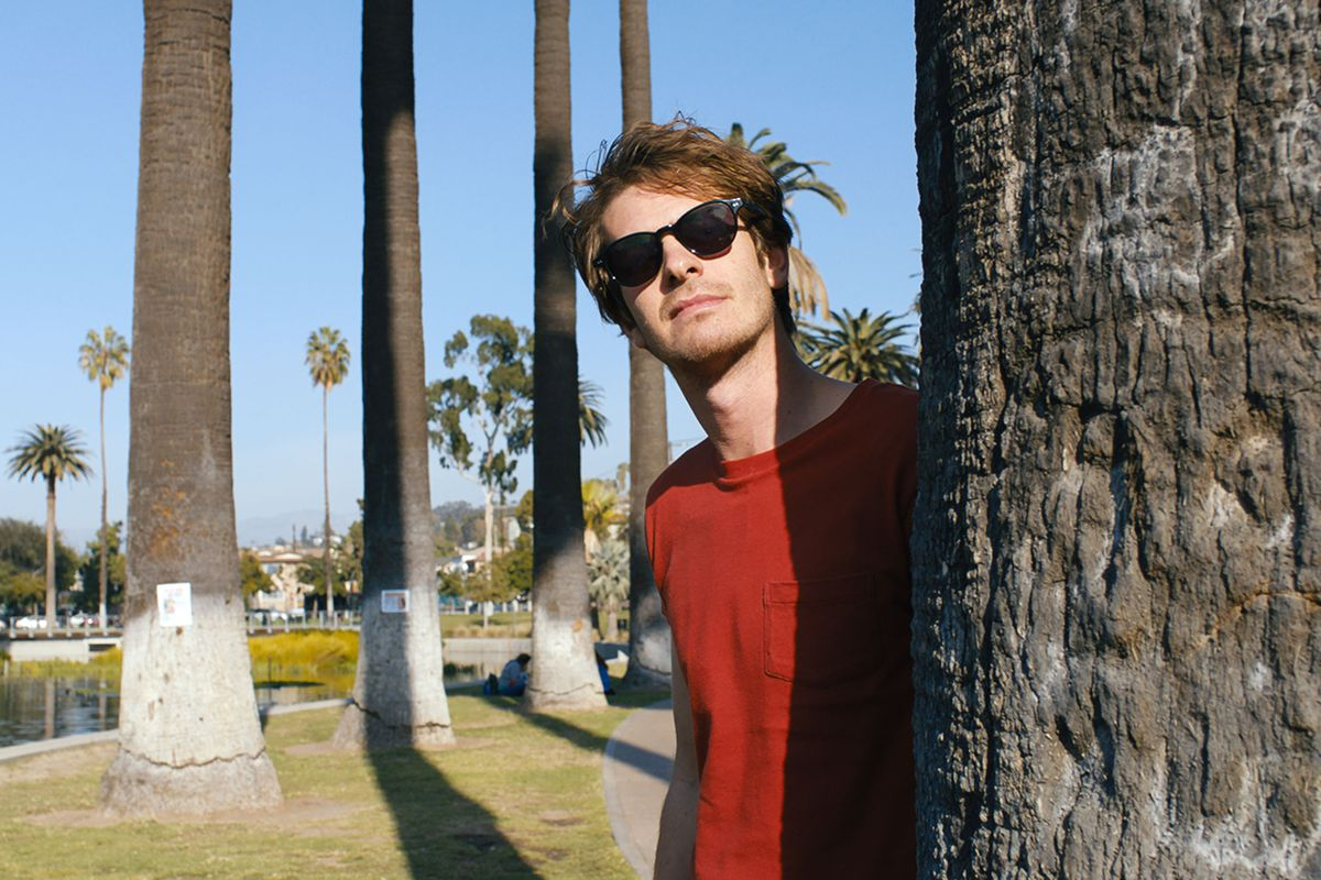 andrew garfield peeks from behind a palm tree with his sunglasses on