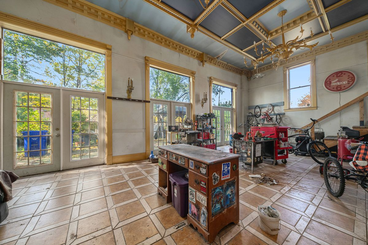 A huge sun room with gold-pained coffered ceiling and tons of bike equipment spread out on the tiled floor.