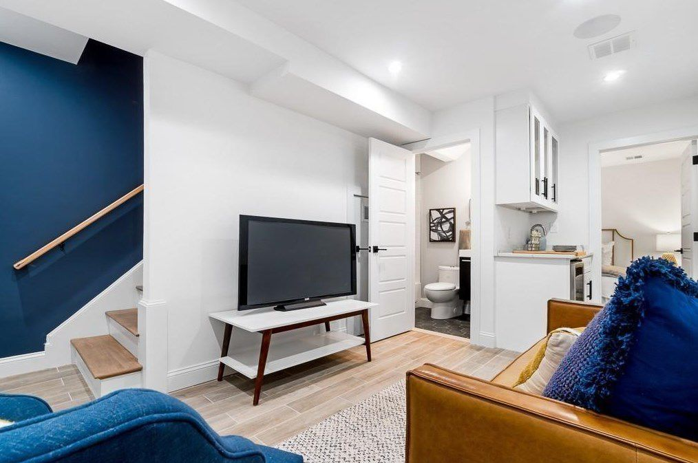 A basement with furniture and carpeting, and there's a stairwell leading into it.