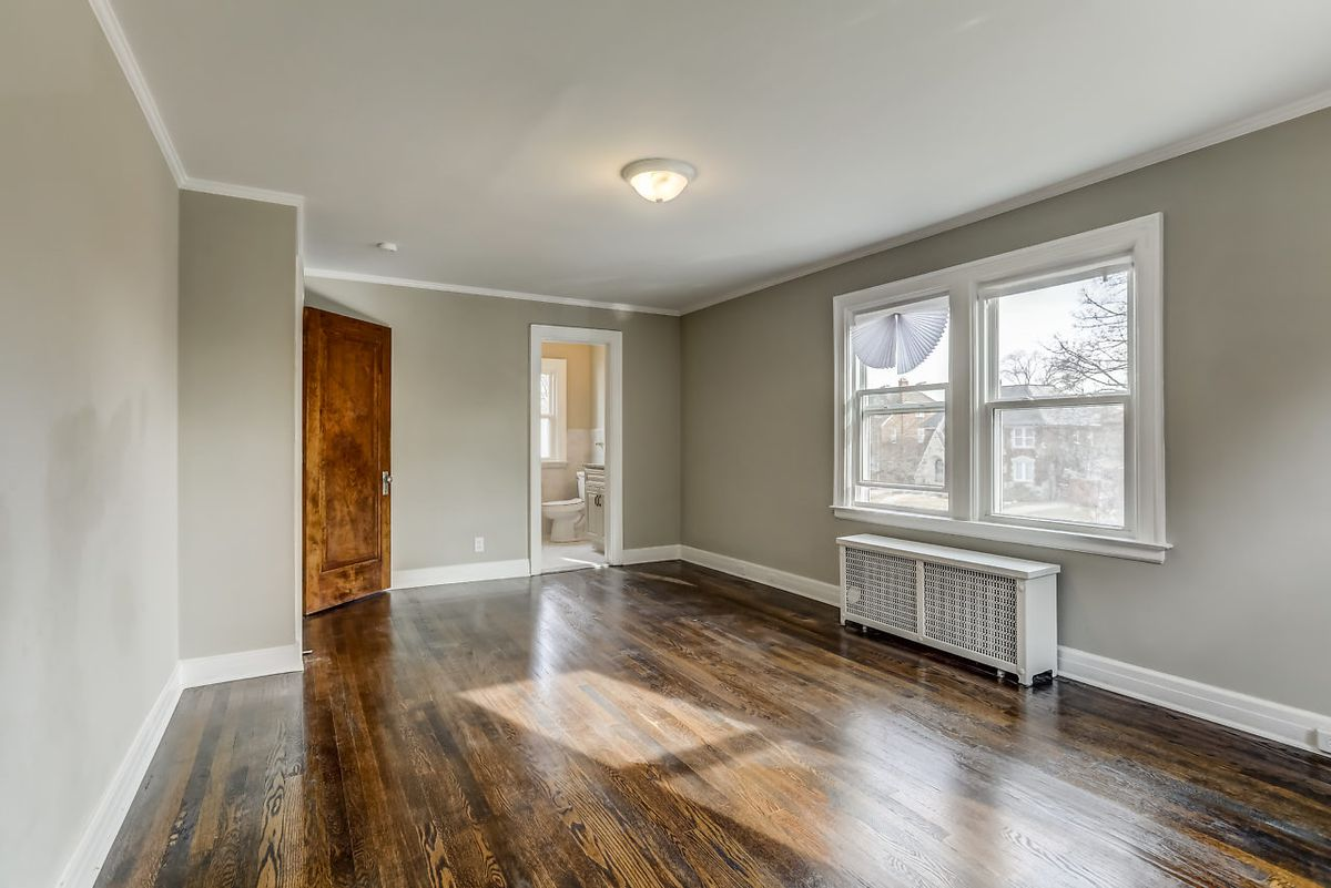 A big empty room with hardwood floors and olive colored walls. An open door leads to a bathroom.