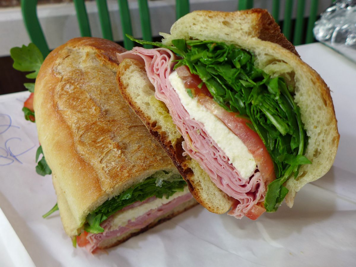 A very long luncheon meat and fresh mutz sandwich, cut in half with the halves lying across each other like two legs.