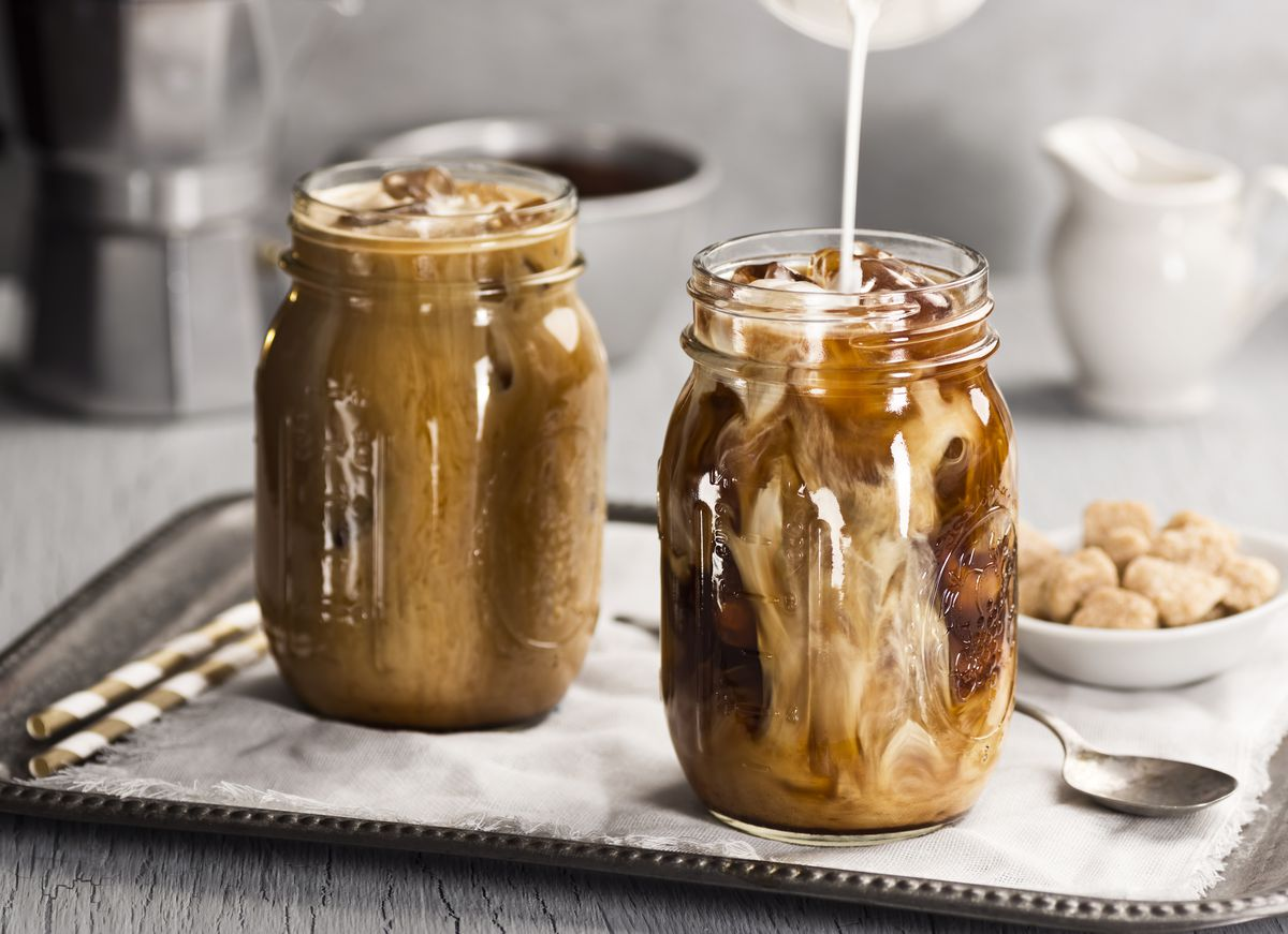 Milk being poured into mason jars filled with iced coffee.