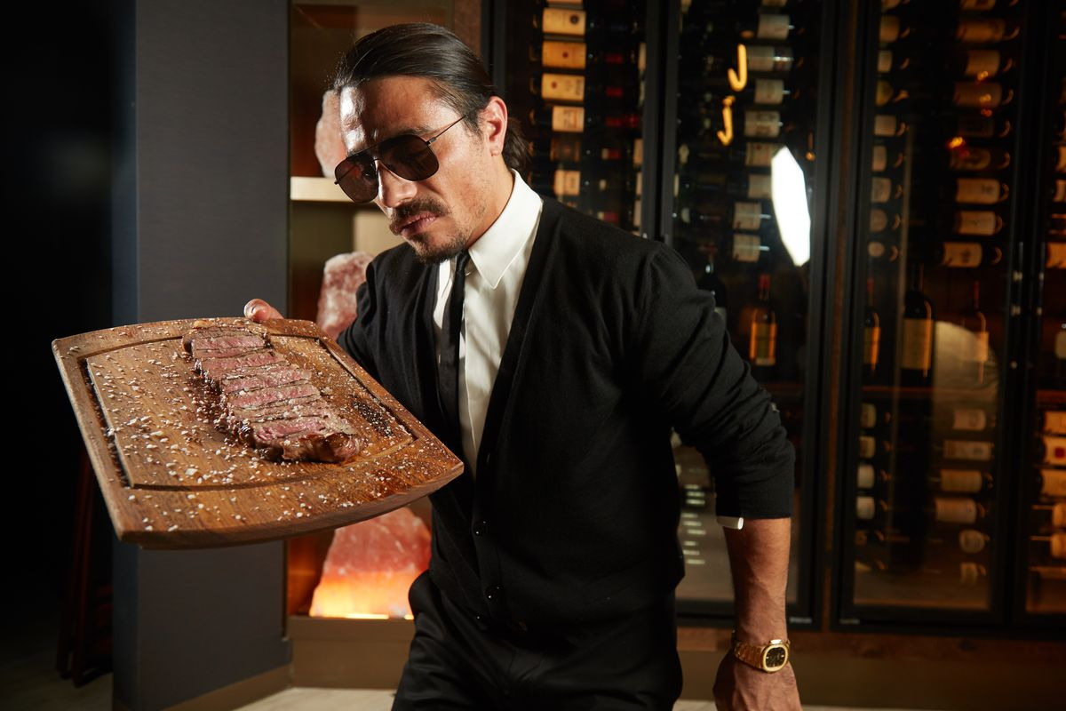 Salt Bae lovingly holding a chopping board topped with a steak, while wearing a suit, tie, and sunglasses