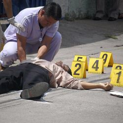 Forensic workers examine the body of human rights District Attorney Manuel Eduardo DÍaz Mazariegos after he was gunned down in Choluteca, Honduras, Monday Sept. 24, 2012. A day earlier, Antonio Trejo Cabrera, a prominent Honduran human rights lawyer was also gunned down in the capital city of Tegucigalpa. (AP Photo)