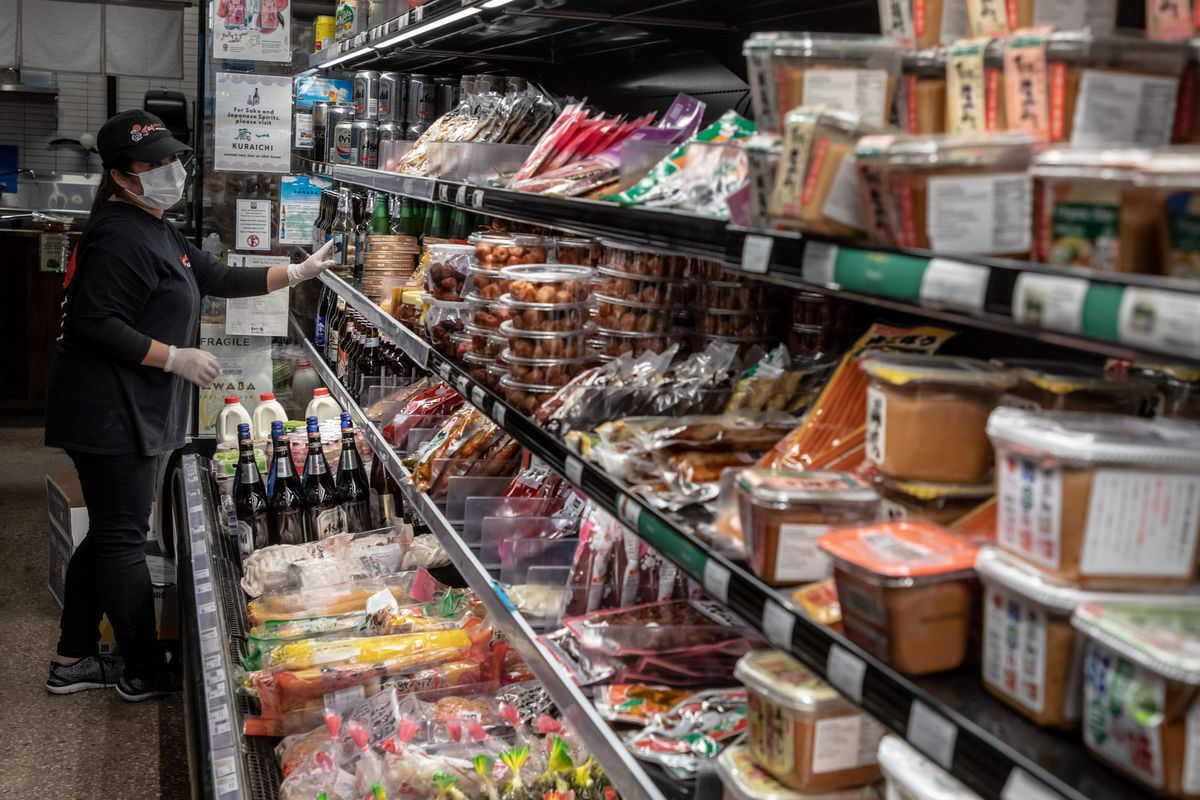 An employee wearing a black hat checks on stock at a refrigerated section at Sunrise Market.