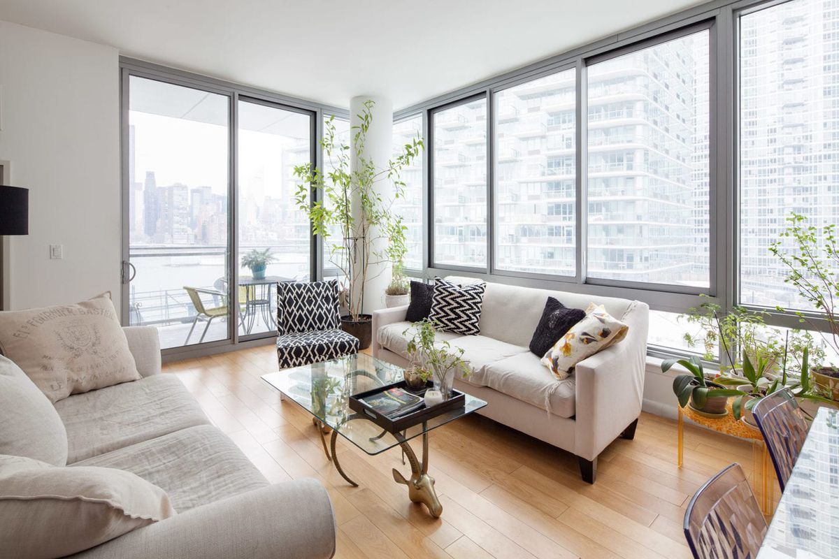 A living area with two couches, a glass coffee table, floor-to-ceiling windows, and several planters.