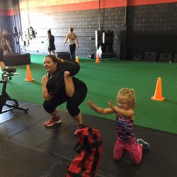 Jennifer and Ashley Taylor do sandbag squats during the family fitness class Sunday at Pure Workout that raised money for the family of Memorez and Jase Rackley, who were killed in a shooting last Tuesday.
