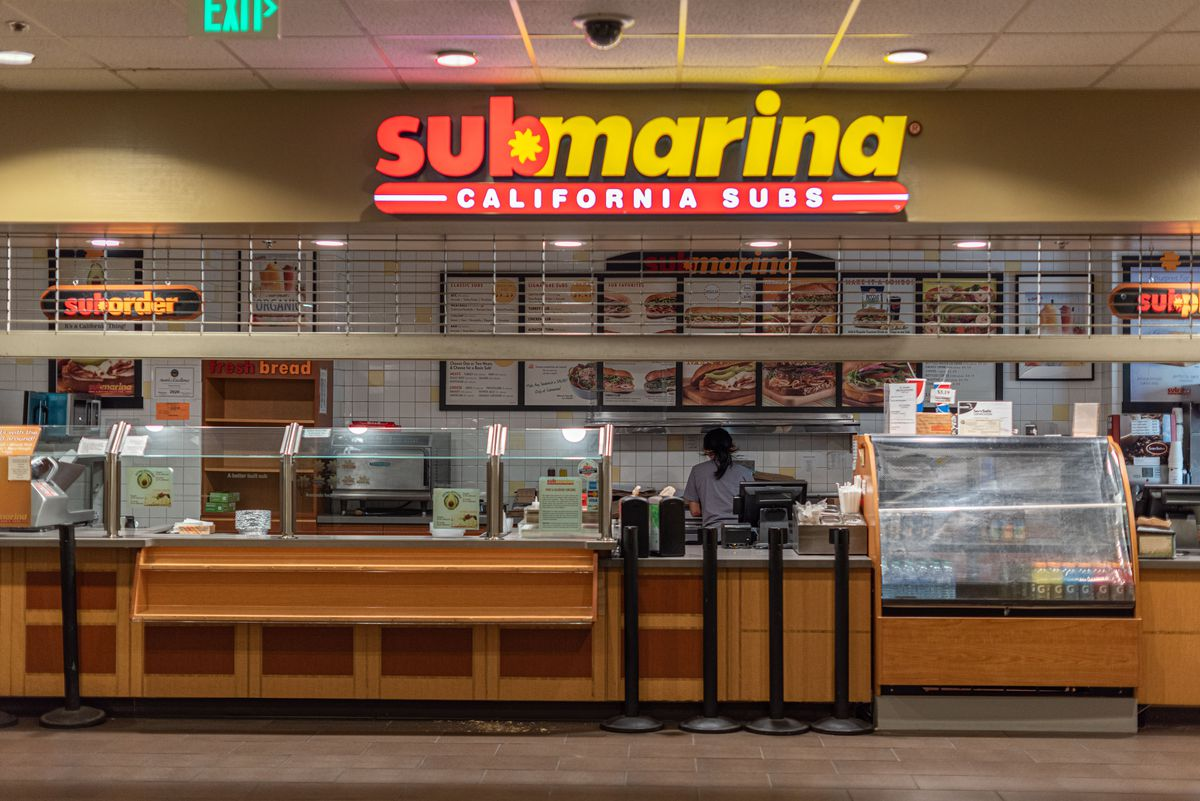 A semi-closed fast casual sandwich restaurant with a lone worker inside.