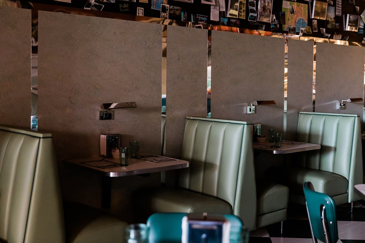 The booths are upholstered green with a 1950s look with linoleum tables with chrome edges set between each seat.