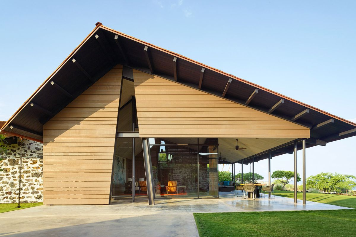 Exterior of house with asymmetrical pitched roof and concrete patio.