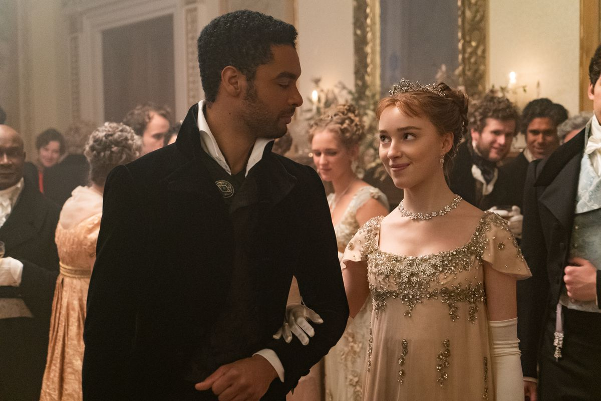 A couple in Regency clothing link arms and gaze at each other at a ball.