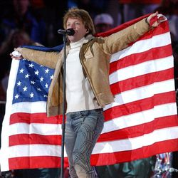 Jon Bon Jovi holds up an American flag as he performs during the Salt Lake 2002 Winter Games closing ceremony at the University of Utah's Rice-Eccles Stadium on Sunday, Feb. 24, 2002.