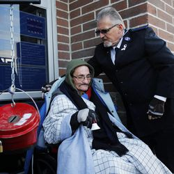 Doug Holladay, a former Salvation Army worker who is fighting terminal lung cancer, rings a bell for donations a final time in Riverdale, Thursday, Dec. 5, 2013. Longtime friend Raymond Young of the Salvation Army places a coat on his shoulders.