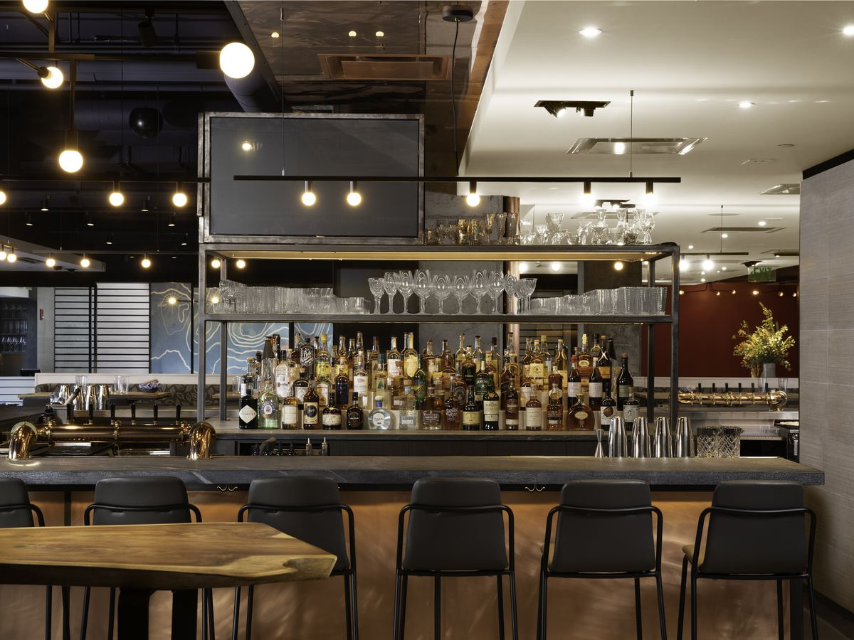 A wide shot of bar seating and tiered liquor bottles at Alcove restaurant
