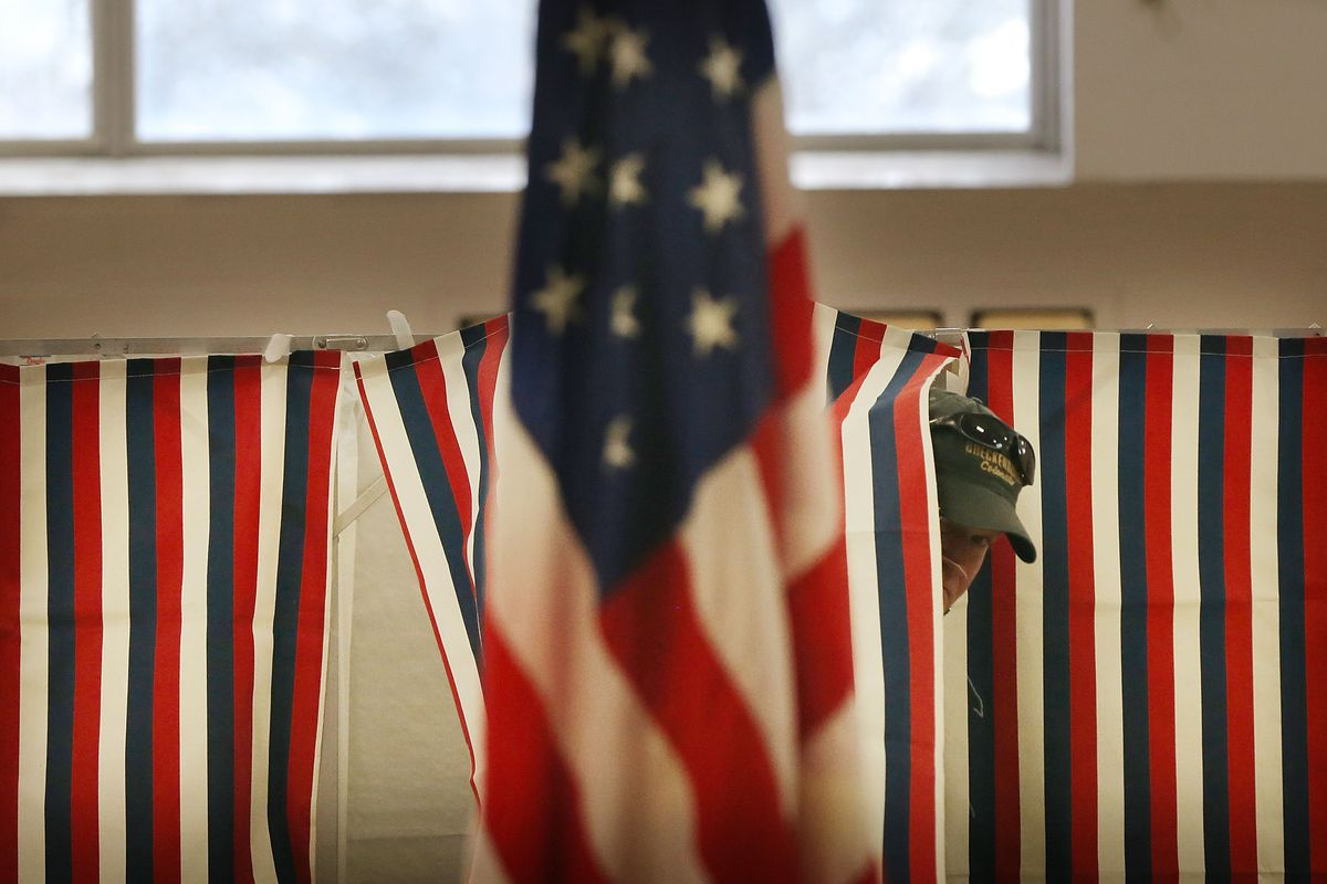 A man exits a voting booth.