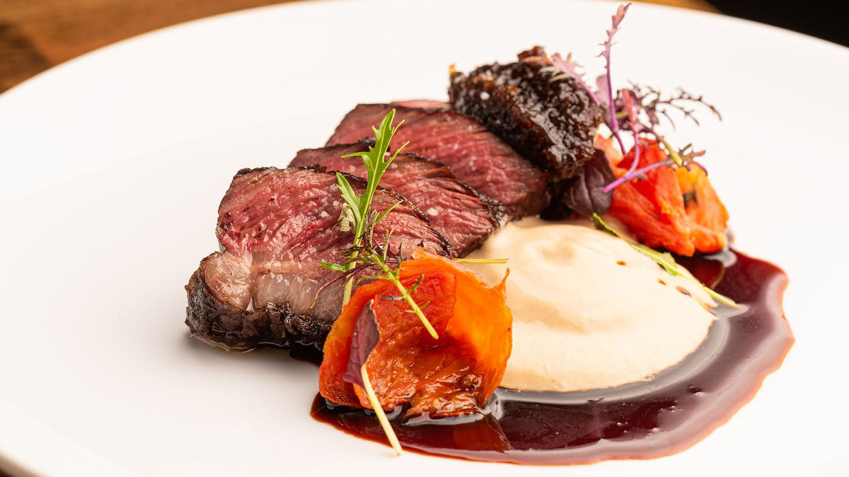 A rare steak sits well-plated at a fine dining restaurant.