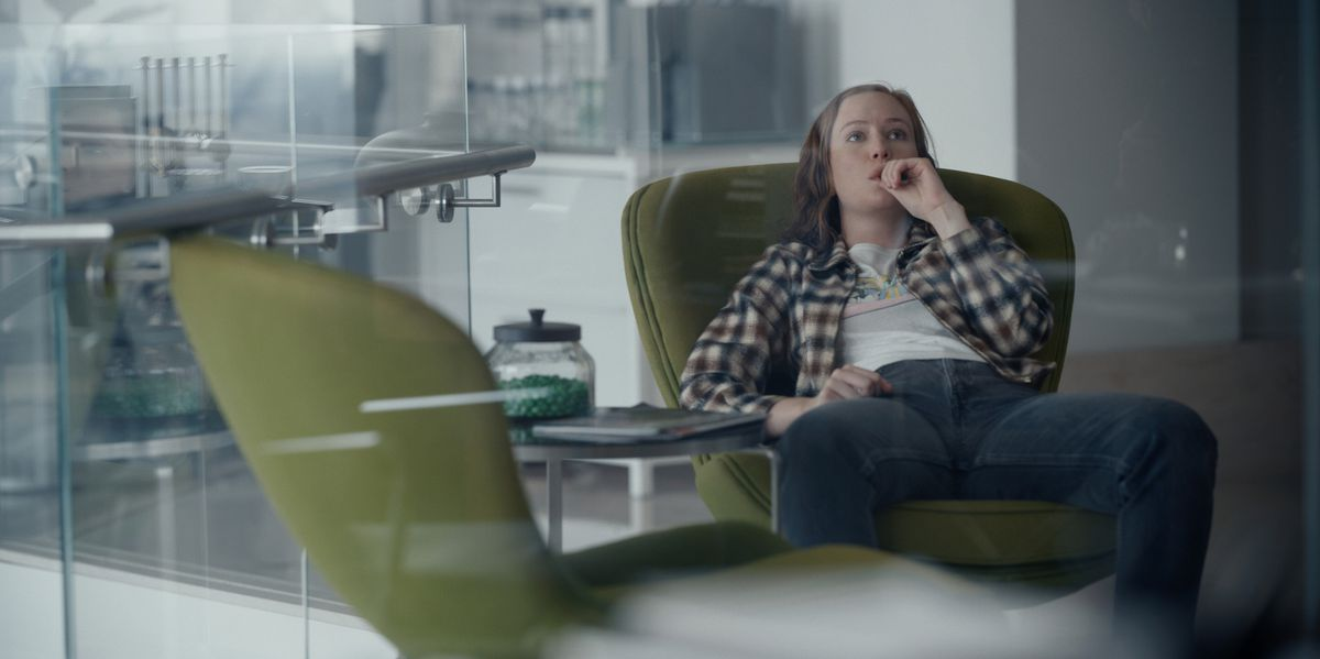 Hannah Einbinder slouches in a green chair behind a glass wall in Hacks