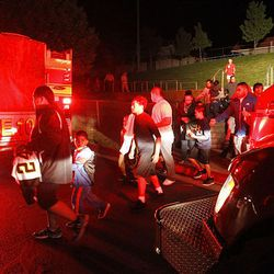 Salt Lake City Fire evacuate fans and players from the   East High School stadium after a fire broke out in a facility building at the field in Salt Lake City  Friday, Aug. 31, 2012. The game will be finished saturday morning.