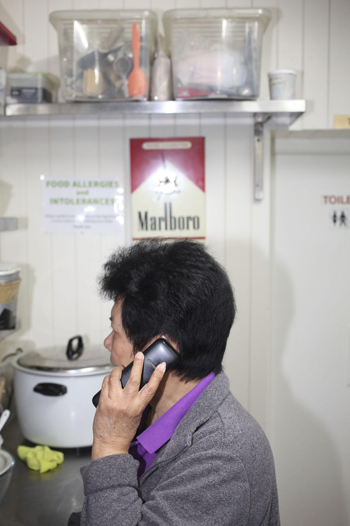 Thelma Kularbwong, front-of-house, on the phone at Singburi