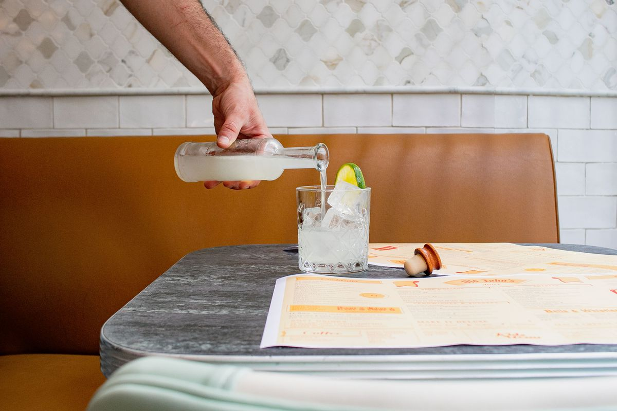 A hand holds a long glass jar and pours a cloudy white liquid into a glass with ice and a lime garnish sitting on a grey tabletop