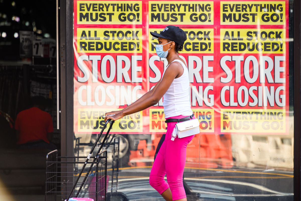 """A person in a mask pushes a shopping cart past signs in a store window that read, """"Everything must go! All stock reduced! Store closing!"""""""