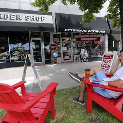 Eric Burkhart waits in a chair outside of City Barbers as his friend gets a haircut at the shop on Broadway between 200 East and 300 East in Salt Lake City on Thursday, June 18, 2020. City Barbers provides the outdoor chairs to help maintain social distancing inside during the COVID-19 pandemic.