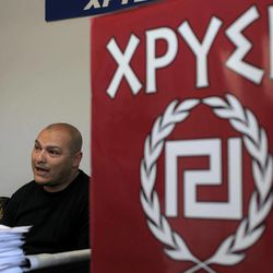"""In this Thursday April 26, 2012 photo Giorgos Germanis, a candidate of extreme far-right Golden Dawn party speaks during a interview with The Associated Press next to a banner with the twisting Maeander, an ancient Greek decorative motif that the party has adopted as its symbol, in the suburban town of Artemis, 25 kilometers (15 miles) east of Athens. Reeling from a vicious financial crisis that has cost them pensions and jobs, Greeks have been turning away in droves from the mainstream politicians they feel have let them down. Firmly on the fringe of the right since it first appeared 20 years ago, Golden Dawn garnered a meager 0.23 percent in the 2009 elections. But its popularity has shot up over the past few months and support stood at about 5 percent in recent opinion polls, well above the 3 percent threshold needed to enter parliament. Sign reads: """"Golden""""."""