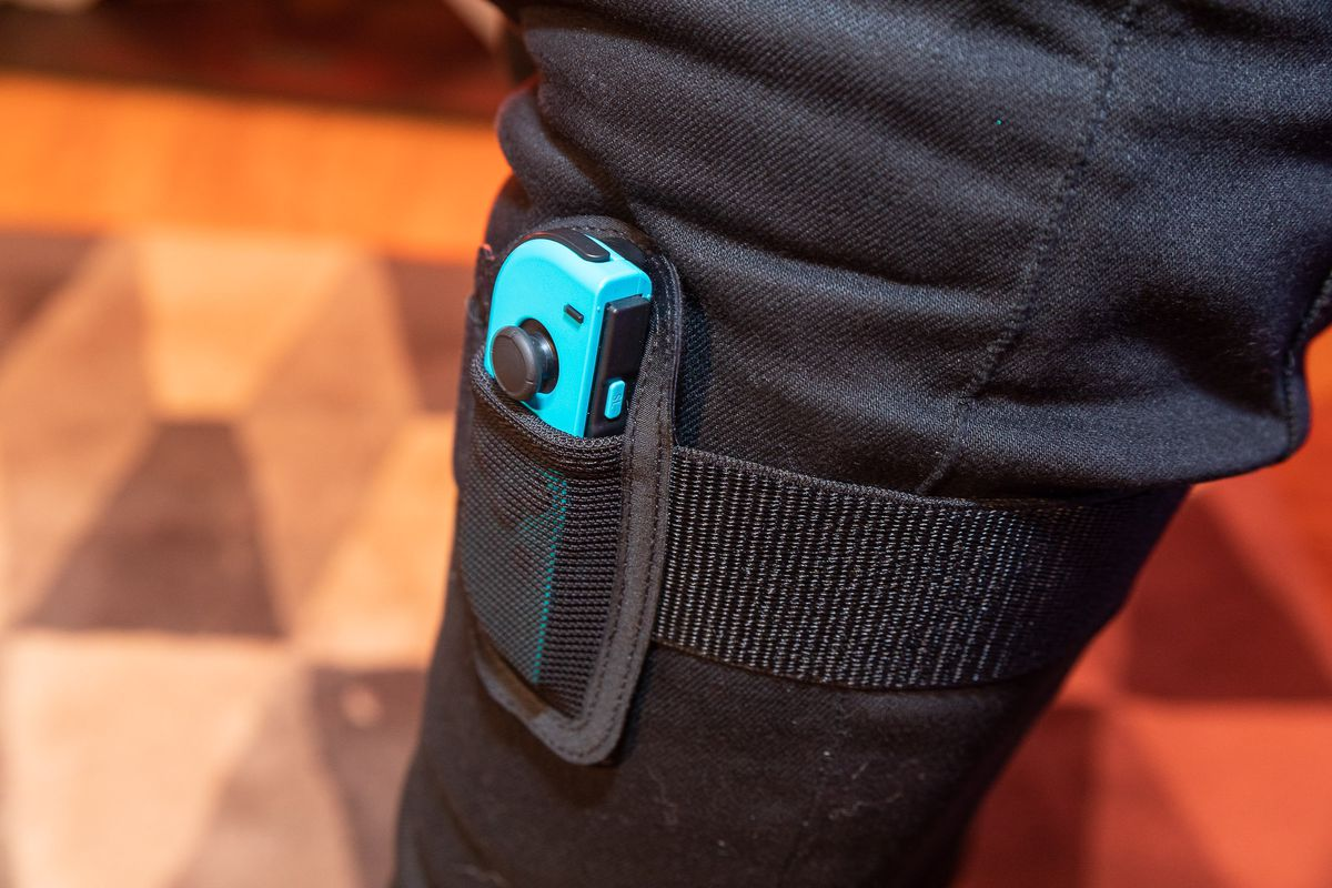 a close-up of a blue Nintendo Switch Joy-Con controller in the leg strap for Ring Fit Adventure