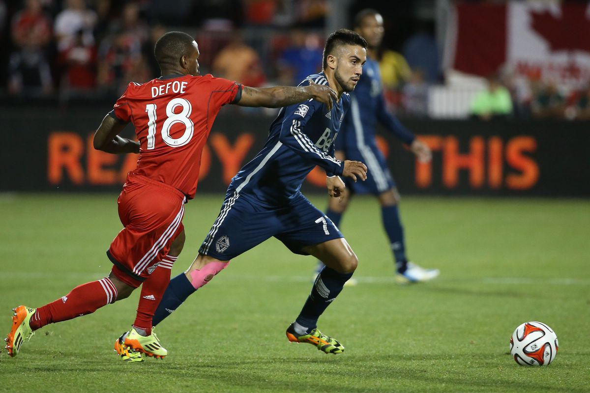 Jermain Defoe (L) challenges Pedro Morales  for the ball in a match on July 16th, 2014. The match ended in a one all draw