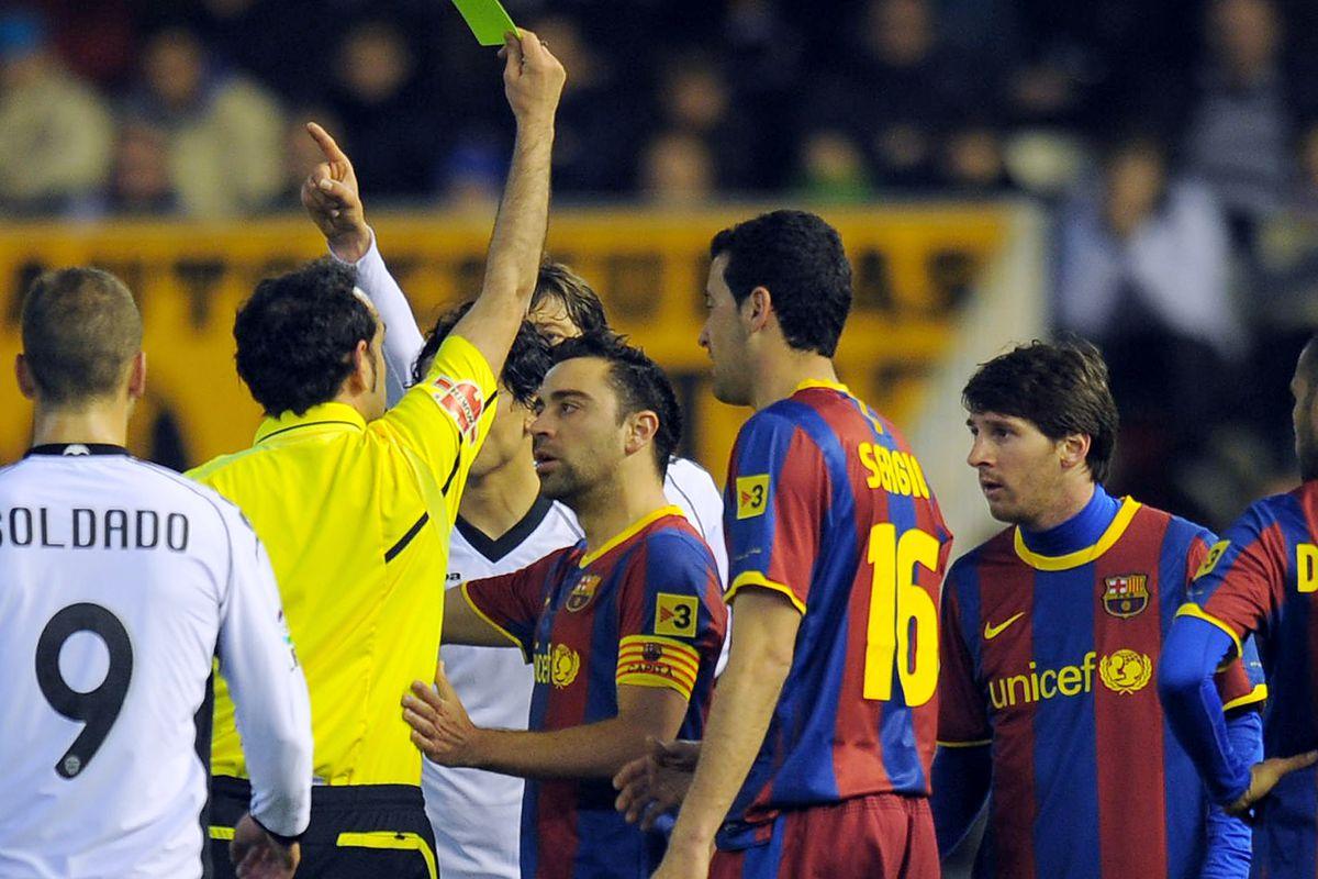 Referee Iturralde Gonzalez shows a yello