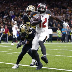 Tampa Bay Buccaneers wide receiver Chris Godwin (12) scores a touchdown against New Orleans Saints free safety Marcus Williams (43) and strong safety Vonn Bell (24) in the first half of an NFL football game in New Orleans, Sunday, Oct. 6, 2019.